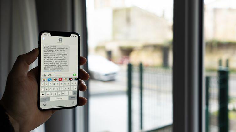Une personne montre sur son téléphone portable le texto envoyé par le gouvernement pendant l'épidémie de coronavirus, le 17 mars 2020 à Bordeaux. (CONSTANT FORME-BECHERAT / HANS LUCAS / AFP)