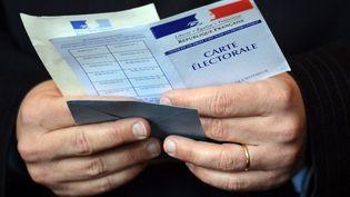 Un électeur tient son bulletin de vote ainsi que sa carte d'électeur, le 22 avril 2012, à Paris. (ERIC FEFERBERG / AFP)
