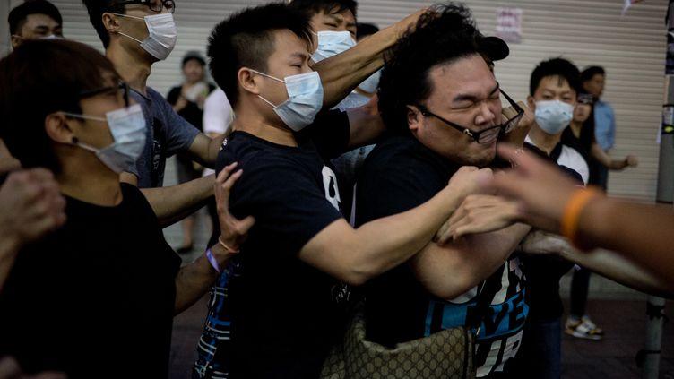 Un manifestant pro-démocratie est frappé par un groupe d'hommes masqués, à Causeway Bay (Hong Kong), le 3 octobre 2014. (ALEX OGLE / AFP)