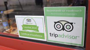 Des stickers du site TripAdvisor sur la devanture d'un restaurant à Paris. (SERGE ATTAL / ONLY FRANCE / AFP)