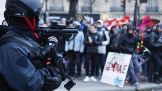 Un policier tenant un LBD face à des manifestants à Paris, le 10 décembre 2019. (ZAKARIA ABDELKAFI / AFP)