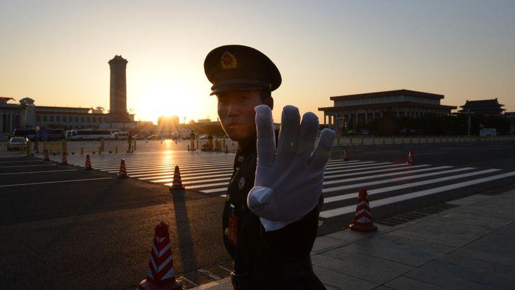 Un policier chinois tente d'empêcher un photographe d'immortaliser la place Tiananmen (Pékin), le 8 novembre 2012. (MARK RALSTON / AFP)