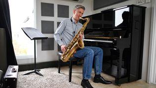 Le saxophoniste Dave O'Higgins, jouant de son instrument dans son studio londonien. (JUSTIN TALLIS / AFP)