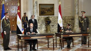Le président égyptien Abdel Fattah Al-Sissi, le ministre français de la Défense Jean-Yves Le Drian et son homologue égyptien signe l'acghat d'avions Rafale l'Egypte au Caire le 16 février 2015 (MARTIN BUREAU / AFP)
