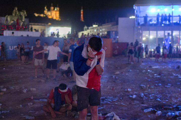 Des supporters français présents dans la fanzone de Lyon réagissent àladéfaite des Bleus enfinale contre le Portugal, le 10 juillet 2016 (ROMAIN LAFABREGUE / AFP)