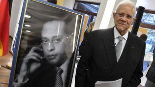Nasser Kotby se tient a coté du portrait de son oncle, le médecin égyptien Mohamed Helmy, à Berlin le 26 octobre 2017. (John MACDOUGALL / AFP)