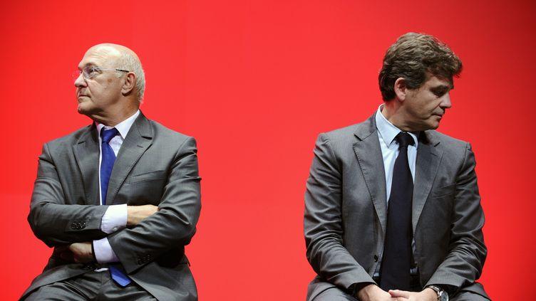 Michel Sapin (à gauche) et Arnaud Montebourg, le 24 septembre 2013, à Bordeaux. (NICOLAS TUCAT / AFP)