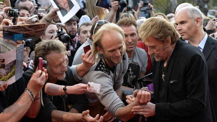 Johnny Hallyday signe des autographes à Beaune (Côte-d'Or). (JEAN-PHILIPPE KSIAZEK / AFP)