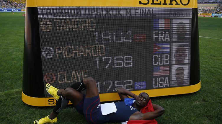 Teddy Tamgho pose devant son record de France du triple saut à 18,04 m, lors des Mondiaux de Moscou (Russie), le 18 août 2013. (ADRIAN DENNIS / AFP)