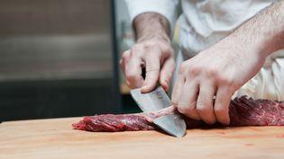Un boucher prépare une pièce de boeuf le 15 juillet 2011. (ALEXANDER PORTER C/AFP)