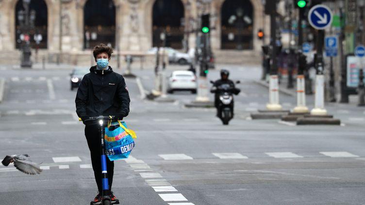 Un homme porte un masque sur sa trotinnette électrique, le 4 mai 2020 à Paris. (LUDOVIC MARIN / AFP)