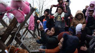 Migrants bloqués devant la clôture de la frontièregréco-macédonienne près du village grec d'Idomeni, le 1er décembre 2015. (GIANNIS PAPANIKOS / AP / SIPA)