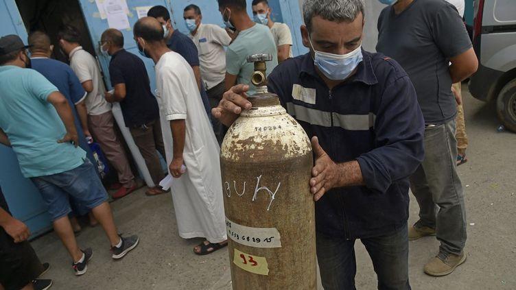 Des Algériens attendent de recevoir des bouteilles d'oxygène offertes par une entreprise privée pour les patients atteints de Covid-19à Blida, au sud d'Alger, le 28 juillet 2021. (RYAD KRAMDI / AFP)