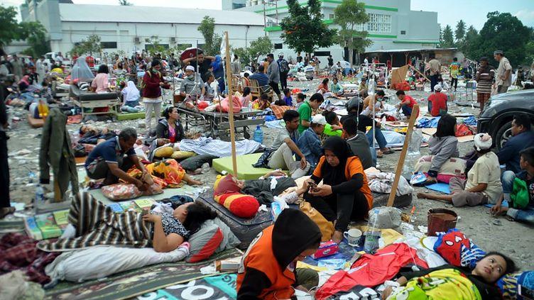 Les hôpitaux étant dépassés par l'afflux de victimes, beaucoup de patients sont soignés à l'extérieur des établissements, comme ici à Palu, sur l'île de Célèbes (Indonésie). (MUHAMMAD RIFKI / AFP)