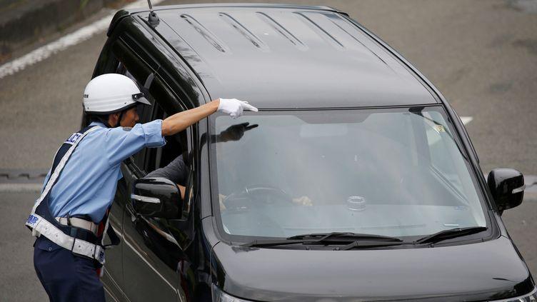 Un policier oriente un conducteur, le 26 juillet 2019, à Sagamihara (Japon). (ISSEI KATO / REUTERS)