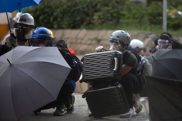 Des manifestants se protègent des gaz avec des parapluies et des valises, le 5 août 2019 à Hong Kong. (ISAAC LAWRENCE / AFP)