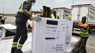 Des travailleurs déchargent une cargaison de vaccin AstraZeneca contre le Covid-19 à l'aéroport d'Abidjan, en Côte d'Ivoire, le 26 février 2021. (SIA KAMBOU / AFP)