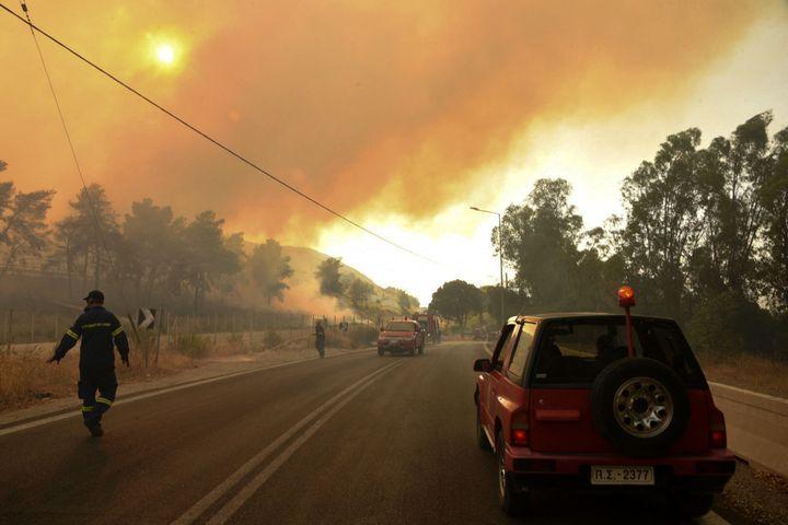 Des pompiers tentent d'éteindre un feu de forêt près de Patras, en Grèce, le 31 juillet 2021. (STR / EUROKINISSI / AFP)