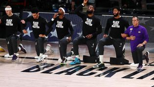 Les Los Angeles Lakers d'Anthony Davis (2e en partant de la droite) et LeBron James (3e en partant de la droite) posent le genou à terre pour le mouvement BlackLivesMatter, le 12 septembre 2020 à Lake Buena Vista (Floride).  (MICHAEL REAVES / GETTY IMAGES NORTH AMERICA / AFP)