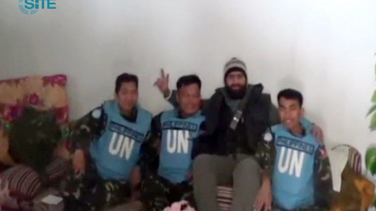 Capture d'écran d'une vidéo diffusée le 8 mars 2013 par le SITE Intelligence group, montrant un rebelle syrien avec des observateurs de l'ONU philippins capturés deux jours plus tôt dans le Golan. (SITE / AFP)