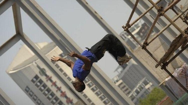 Un Yamakasi fait une performance sur le site de l'ambassade de France en Chine, mai 2010  (PETER PARKS / AFP)