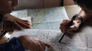 Un garde-côtes japonais étudie une carte dans un avion de recherche du vol MH370, le 15 mars 2014. (EDGAR SU / REUTERS)