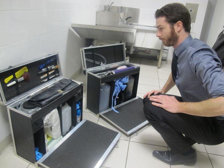 Axel prépare son matériel afin d'effectuer un soin à une défunte. (ELISE LAMBERT/FRANCETV INFO)