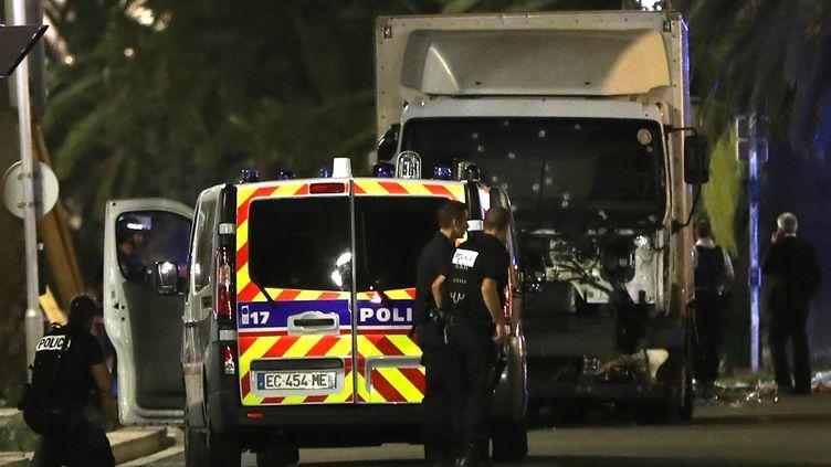 Des policiers sur la promenade des Anglais, à Nice (Alpes-Maritimes), à proximité du camion meurtier qui a tué 84 morts, le 14 juillet 2016. (VALERY HACHE / AFP)