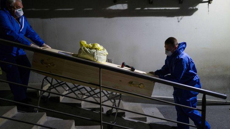 Des employés des pompes funèbres transportent le cercueil d'une victime du coronavirus, le 1er avril 2020 (illustration). (SEBASTIEN BOZON / AFP)
