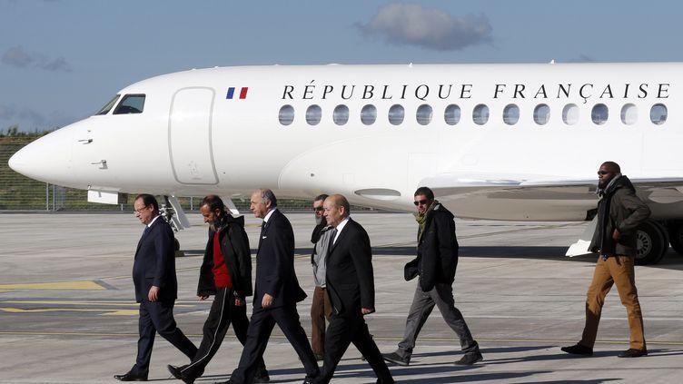 Le président de la République, François Hollande, les ministres Laurent Fabius et Jean-Yves Le Drian, et les ex-otages, le 31 octobre 2013 à Villacoublay (Yvelines). (FRANÇOIS GUILLOT / AFP)