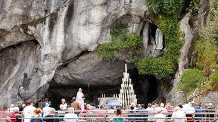 Des fidèles assistent à une messe devant la grotte de Massabielle, à Lourdes, le 16 juillet 2021. (LUDOVIC MARIN / AFP)