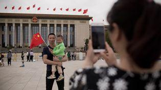 Une famille chinoise sur la place Tiananmen à Pékin. (NICOLAS ASFOURI / AFP)
