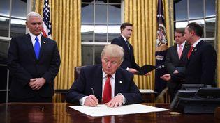 Donald Trump dans le bureau ovale de la Maison Blanche, après son investiture comme président des Etats-Unis, le 20 janvier 2017. (JIM WATSON / AFP)