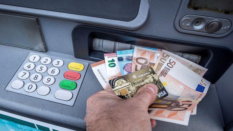 Un homme récupère de l'argent liquide à un distributeur de billets à Lille (Nord), 4 janvier 2017. (PHILIPPE HUGUEN / AFP)