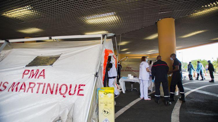 Des pompiers et des urgentistes devant une tente de tri mise en place pour les patients Covid en détresse respiratoire, à l'hôpital Pierre Zobda-Quitman, le CHU de Fort-de-France, le 30 juillet 2021. Seulement 15% des habitants du territoire caribéen de Martinique sont vaccinés. Un nouveau confinement de 3 semaines a été décrété depuis ce 30 juillet. (LIONEL CHAMOISEAU / AFP)