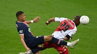 L'attaquant du PSG Kylian Mbappé à la lutte avec le défenseur monégasque Djibril Sidibé en finale de la Coupe de France, mercredi 19 mai 2021 au Stade de France (Seine-Saint-Denis). (ANNE-CHRISTINE POUJOULAT / AFP)