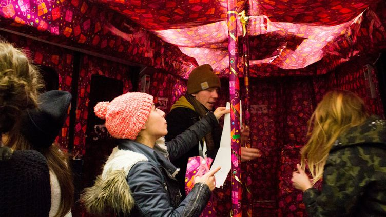 Des artistes de la sociétéSisaprod collent du papier cadeau dans une rame du métro de la ligne 8 à Paris le 20 décembre 2013. (SISAPROD)