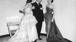 Le couturier Christian Dior avec deux de ses mannequins avant la présentation de sa dernière collection, le 24 avril 1950. (AFP)