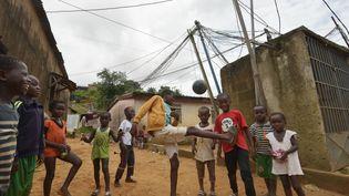 Des enfants jouent au football dans un quartier d'Abidjan, en Côte d'Ivoire. (SIA KAMBOU / AFP)