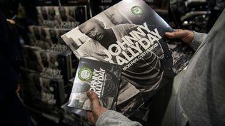 Un fan achète l'album et le vinyle du dernier disque de Johnny Hallyday, le 19 octobre. (CHRISTOPHE ARCHAMBAULT / AFP)