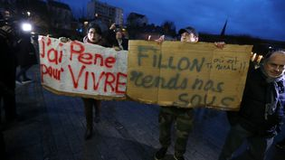 Des manifestants brandissent des pancartes en marge d'un déplacement de François Fillon à Troyes, le 7 février 2017. (FRANCOIS NASCIMBENI / AFP)