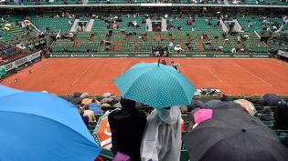 Des spectateurs du tournoi de Roland-Garros s'abritent sous un parapluie, à Paris. (ERIC FEFERBERG / AFP)