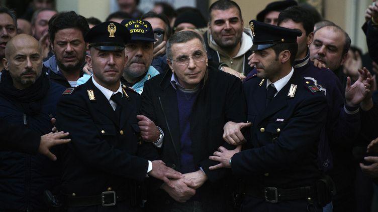 Michele Zagaria, chef du puissant clan Casalesi de la mafia napolitaine, escorté par des policiers à Castera, en Italie, après son arrestation, le 7 décembre 2011. (ROBERTO SALOMONE / AFP)