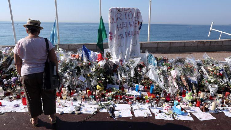 Une femme rend hommage aux victimes de l'attentat de Nice (Alpes-Maritimes), le 19 juillet 2016. (VALERY HACHE / AFP)