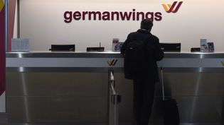 Un homme attend au comptoir d'enregistrement de la compagnie aérienne Germanwings, à l'aéroport de Bonn-Cologne, le 24 mars 2015. (PATRIK STOLLARZ / AFP)