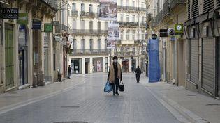 Une passante dans le centre-ville de Montpellier, en mars 2020. Photo d'illustration. (GIACOMO ITALIANO / MAXPPP)