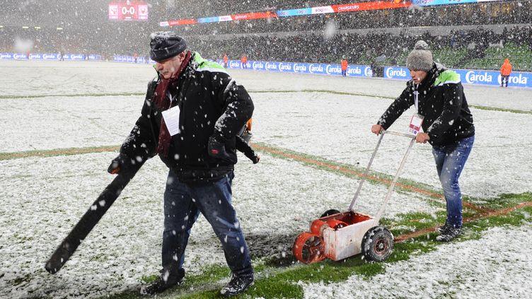 Des stadiers enlèvent la neige de la pelouse du stade Saint-Symphorien lors de Metz-Nice, le 31 janvier 2015. (JEAN-CHRISTOPHE VERHAEGEN / AFP)