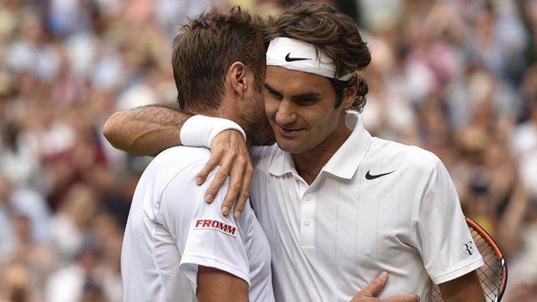 Roger Federer étreint son compatriote Stan Wawrinka sur le Centre court de Wimbledon (TOBY MELVILLE / POOL)