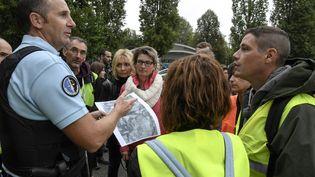 Un gendarmedétaille les zones de recherches et les règles à respecter pour la battue citoyenne àPont-de-Beauvoisin (Isère), le 2 septembre 2017. (PHILIPPE DESMAZES / AFP)