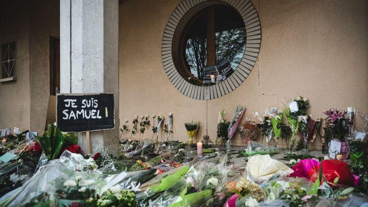 Des fleurs déposées devant le collège de Conflans-Sainte-Honorine (Yvelines) où Samuel Paty enseignait, le 17 octobre 2020. (SAMUEL BOIVIN / NURPHOTO)
